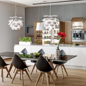 Drewniana podłoga, nogi eamesowkich krzeseł oraz wysoka zabudowa z dekorem w pionowym układzie słojów. Mnogość elementów w kolorze drewna tonuje biała wyspa kuchenna. Fot. Peka.