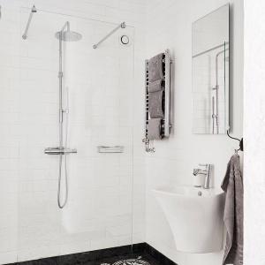 W łazience biel łączy się z czernią. Ściany wykończono prostymi płytkami ceramicznymi, a podłogę zdobią piękne ciemne, wzorzyste płytki. Fot. Stadshem.se/Jonas Berg.