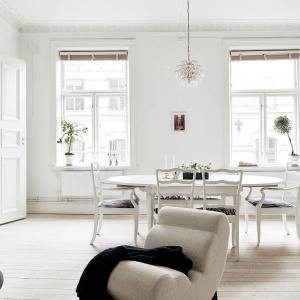 Białe mieszkanie dodatkowo rozświetlają duże okna, pozbawione firan. Fot. Stadshem.se/Jonas Berg.