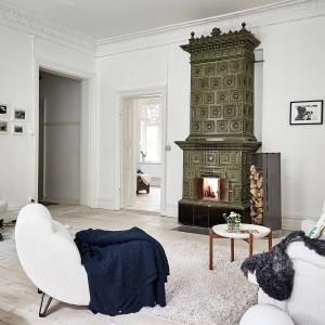 W salonie wzrok przyciąga tradycyjny piec kaflowy, stanowiący istotny element aranżacji wnętrza. Idealnie harmonizuje on z ozdobnymi sztukateriami wokół sufitu. Fot. Stadshem.se/Jonas Berg.