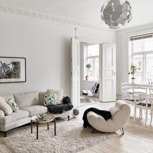 Wystrój mieszkania bazuje na elementach pozostałych z oryginalnego wyposażenia wnętrza, uzupełnionych o eleganckie dodatki, jasne kolory i klasyczne meble. Fot. Stadshem.se/Jonas Berg.