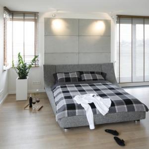 Tapicerowane łóżko w szarym kolorze to nowoczesny i niezwykle modny element wnętrza. Nad szarym zagłówkiem dobrze prezentuje się beton architektoniczny. Projekt: Agnieszka Ludwinowska. Fot. Bartosz Jarosz.
