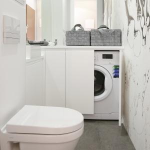 Mała i wąska łazienka z pralką – całą ścianę wokół sedesu zajmują ukryte półki. Projekt: Karolina Łuczyńska. Fot. Bartosz Jarosz.