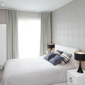 Szarości to sprawdzony sposób na rozjaśnienie sypialni. Jasny, rozbielony szary kolor przyciąga naturalne światło jak magnes, a rozjaśnić jeszcze bardziej wnętrze pomoże łóżko tapicerowane białą tkaniną. Projekt: Małgorzata Galewska. Fot. Bartosz Jarosz.