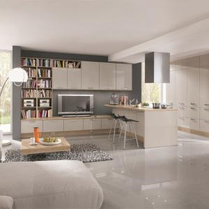 Zabudowa kuchenna jest dopasowana idealnie kolorem i stylistyką do mebli w salonie, a półwysep funkcjonujący jako bar jest ciekawie scalony z meblościanką. Fot. Nobilia.
