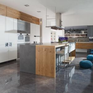 """W tej kuchni wyspa składa się z dwóch części, których odrębność zaakcentowano różnymi materiałami wykończeniowymi. W """"szarej"""" strefie znalazło się miejsce na zlewozmywak, a drewniany blat pełni funkcję baru. Fot. Mebel Rust."""