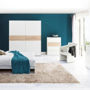 Sypialnia Wenecja marki Szynaka Meble to biel delikatnie ocieplona jasnymi elementami drewna. Kolekcja jest nowoczesna i doskonale wpisze się w skandynawską stylistykę wnętrza. Fot. Szynaka Meble.