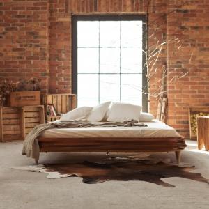 Nałożone na siebie warstwowo płaty drewna tworzą nietypową i jednocześnie elegancką ramę łóżka. Brak zagłówka sprawia, że model ten doskonale nadaje się do ustawienia na środku sypialni. Fot. Gie-el.
