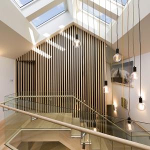 Klatka schodowa, komunikująca piętro z parterem sama w sobie również została bardzo efektownie zaaranżowana. Ażurowe, drewniane deski przedzielają przestrzeń, a zwisające z sufitu, edisonowskie żarówki są mocnym, gustownym, delikatnie loftowym akcentem. Projekt: Mitsuori Architects. Fot. Michael Kai Photography.