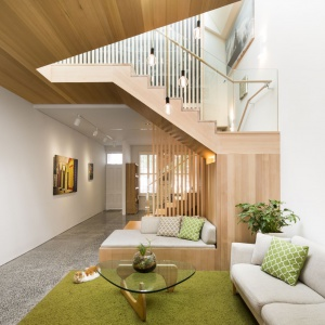 Żywym, wesołym akcentem kolorystycznym jest zielony, włochaty dywan w salonie i towarzyszące mu dekoracyjne poduszki. W otoczeniu wszędobylskiego drewna tworzą obrazek bardzo bliski naturze. Projekt: Mitsuori Architects. Fot. Michael Kai Photography.