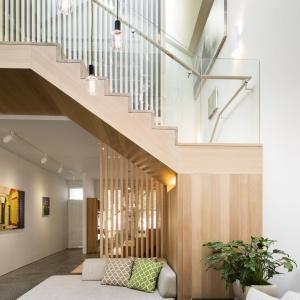 Salon otwarto na dwie kondygnacje. Wzdłuż otwartej klatki schodowej wpada światło, wędrujące od okien dachowych do podłogi w salonie. Projekt: Mitsuori Architects. Fot. Michael Kai Photography.