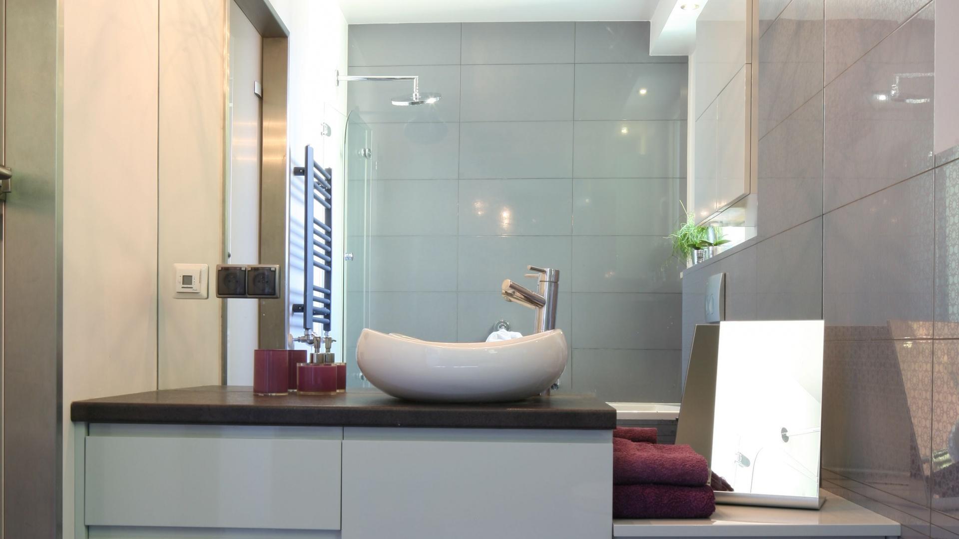 Duże lustro w strefie umywalki oraz płytki ceramiczne w połysku optycznie powiększają kobiecą łazienkę. Fot. Bartosz Jarosz.