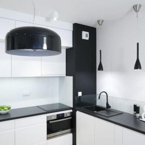 Niewielki aneks kuchenny w małym mieszkaniu urządzono w powiększającej optycznie przestrzeń i zlewającej się ze ścianami bieli. Jej dominację przełamuje czarny blat i czarne dodatki. Projekt: Ewa Para. Fot. Bartosz Jarosz.