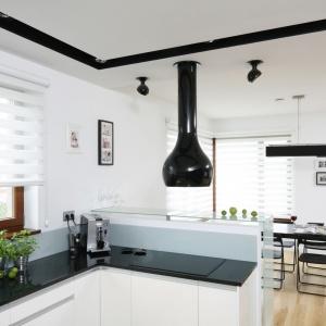 Czarny blat w tej białej kuchni tworzy estetyczną kompozycję z czarnym pasem na suficie w którym zamontowano oświetlenie, dekoracyjnym okapem oraz stołem w jadalni, na którą otwiera się kuchnia. Projekt: Michał Mikołajczak. Fot. Bartosz Jarosz.