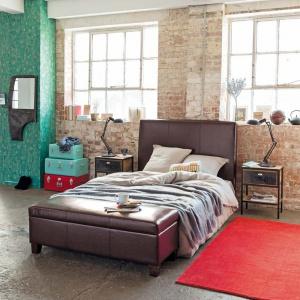 Cegła na ścianie nada wnętrzu loftowego klimatu. Materiał ten doskonale łączy się z łóżkami wykończonymi brązową skórą. Fot. Maison du monde.
