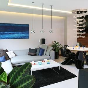 Otwarta przestrzeń na parterze zaprojektowana jest w spójnej kolorystyce bieli, szarości, czerni i brązu. W salonie główne miejsce zajmuje duża, narożna kanapa, której wybarwienie doskonale koresponduje z jasnoszarym kolorem ścian. Projekt: Chantal Springer. Fot. Bartosz Jarosz.
