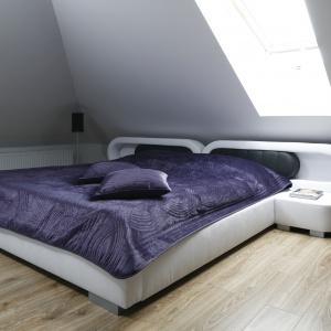 Sypialnię na poddaszu można urządzić nowocześnie. Jasne ściany, minimalna ilość dodatków i łóżko z futurystycznym zagłówkiem sprawią, że wnętrze będzie prezentować się designersko. Projekt: Marta Kilan. Fot. Bartosz Jarosz.
