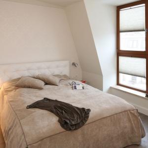 Oryginalny, przezroczysty stolik nocny propozycja do małych sypialni. Na tle masywnego łóżka staje się praktycznie niewidoczny. Projekt: Małgorzata Borzyszkowska. Fot. Bartosz Jarosz.