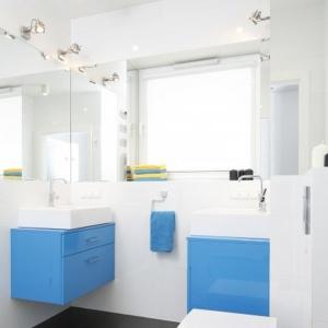 Wąską białą łazienkę wyróżniają podwieszane szafki w niebieskim kolorze. Projekt: Katarzyna Uszok. Fot. Bartosz Jarosz.