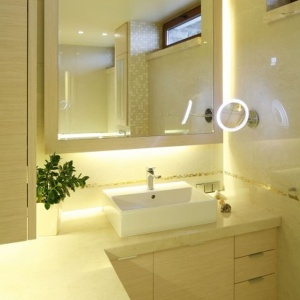 Ciepłe oświetlenie i jasne beże na ścianach sprawiają, że mała łazienka jest bardzo przytulna. Projekt: Małgorzata Borzyszkowska. Fot. Bartosz Jarosz.