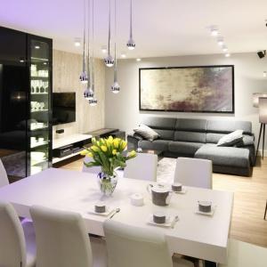 W przestronnym salonie miejsce na jadalnię wygospodarowano na granicy z kuchnią. Organizuje ją duży stół w białym kolorze. Przy nim ustawiono tapicerowane krzesła. Projekt: Monika i Adam Bronikowscy. Fot. Bartosz Jarosz.