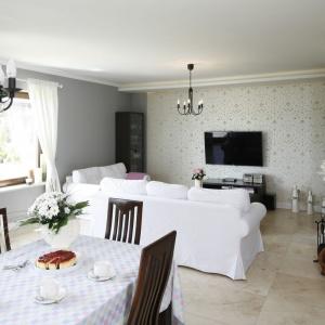 Trawertyn poprowadzony przez całą długość strefy dziennej stanowi klasyczne, piękne połączenie z bielą wnętrza. Szarość nie sprawia już wrażenia smutnego mieszkania dzięki kontrastującej bieli i tradycyjnego drewna.