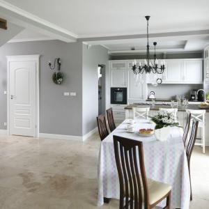 Kuchnia i jadalnia utrzymane w bieli sprawiają wrażenie jasnych i przestronnych. Zwiewność zawiera się w lekkich zasłonach okiennych, przez które wpada tak ważne w kuchniach światło naturalne.