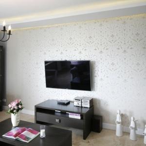 Złoty wzór na ścianie stanowi idealne tło eleganckiej i klasycznej czerni. Podwieszany sufit z LED-owym podświetleniem to wskazówka dla oczu prowadząca właśnie na tą ścianę.