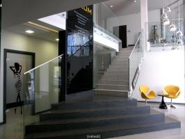 Klatka schodowa biurowca PEKUM z żółtymi fotelikami w strefie wypoczynku