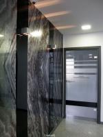 Dekoracyjna ściana przy małej sali konferencyjnej wyłożona tapetą z metalizującym wzorem