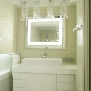 Żyrandole z kryształków świetnie dekorują strefę umywalki. Także rama lustra została dodatkowo podświetlona. Projekt: Małgorzata Borzyszkowska. Fot. Bartosz Jarosz.