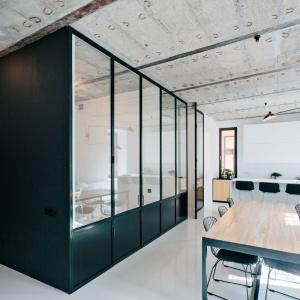 Za zabudową, wzdłuż której ustawiono stół jadalniany, schowano inne funkcje mieszkania, jak sypialnia i gabinet. Projekt: Crosby Studios. Fot. Evgeny Evgrafov.