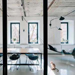 Industrialny klimat we wnętrzu budują loftowe lampy, betonowy sufit i cegła na ścianie. Projekt: Crosby Studios. Fot. Evgeny Evgrafov.