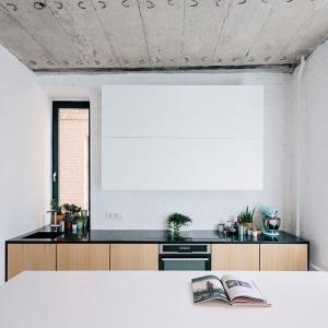 Dolną zabudowę kuchenna wykończono w dekorze drewna i zwieńczono czarnym blatem. Z kolei górne szafki są białe - tak jak ściana za nimi, co sprawia, że są niemal niewidoczne. Projekt: Crosby Studios. Fot. Evgeny Evgrafov.