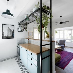 Czarna półka pełni między innymi funkcję kwietnika. Kolorystycznie idealnie harmonizuje z uchwytami mebli kuchennych i loftową lampą. Projekt: Studio Raanan Stern. Fot. Gidon Levin.