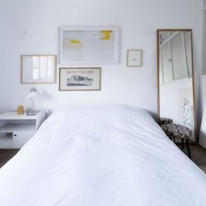 Sypialnia jest jasna i świeża - króluje tutaj biel, a pomieszczenie rozświetla światło wpadające przez przeszkloną przegrodę działową. Projekt: Studio Raanan Stern. Fot. Gidon Levin.
