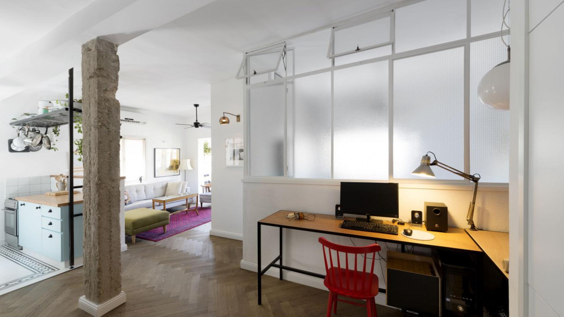 Delikatnie industrialny klimat we wnętrzu buduje nie tylko czarna, metalowa półka w otwartej strefie dziennej, ale również konstrukcyjna kolumna z betonu - jedyna pozostałość po oryginalnym układzie mieszkania. Projekt: Studio Raanan Stern. Fot. Gidon Levin.