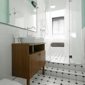 Jasna łazienka została urządzona w podobnej palecie barw, co kuchnia. Przeważa tutaj biel, urozmaicona turkusem, a całość akcentują czarne elementy na podłodze. Projekt: Studio Raanan Stern. Fot. Gidon Levin.