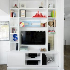 Telewizor w salonie wpasowano we wnękę, otoczoną licznymi, praktycznymi półkami. Mogą one posłużyć za miejsce wyeksponowania dekoracji lub wykorzystane jako biblioteczka. Projekt: Studio Raanan Stern. Fot. Gidon Levin.