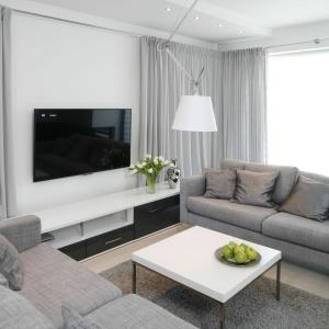 Wśród bieli i szarości zdecydowanie wyróżniają się czarne elementy. Szafka RTV przez zamontowanie czarnego frontu nadaje salonowi więcej nowoczesności.