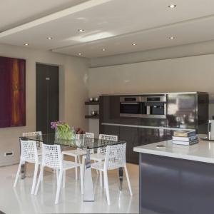 Równolegle do wyspy kuchennej urządzono jadalnię. Jej przestrzeń jest bardzo lekka za sprawą przeźroczystego blatu stołu jadalnianego oraz ażurowych krzeseł mu towarzyszących. Projekt: Nico van der Meulen i Werner van der Meulen. Fot. Barend Roberts and David Ross.