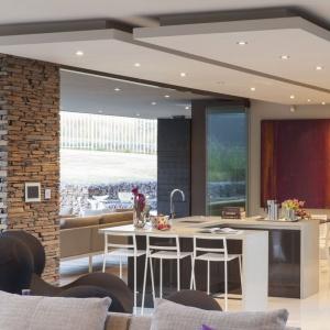 Centrum kuchni jest duża wyspa, która pełni funkcję powierzchni roboczej, w obrębie której urządzono strefę zmywania oraz domowego baru. Projekt: Nico van der Meulen i Werner van der Meulen. Fot. Barend Roberts and David Ross.