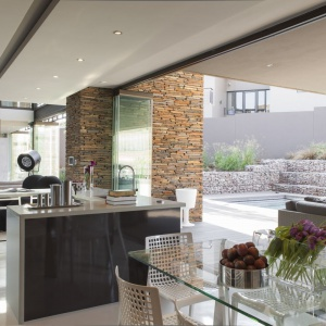 Dom otwiera się na swoje otoczenie, z którym łączą go nie tylko ogromne przeszklenia, ale również wykończenie wnętrza i elewacji budynku takimi samymi materiałami. Projekt: Nico van der Meulen i Werner van der Meulen. Fot. Barend Roberts and David Ross.