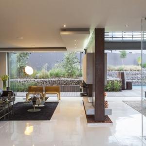 Ścianka działowa, na której zamontowano TV jest elementem dzielącym i spajającym salon i mniejszy salonik. Projekt: Nico van der Meulen i Werner van der Meulen. Fot. Barend Roberts and David Ross.