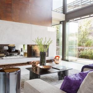 Salon jest niezwykle przestronny - za sprawą nie tylko dużego metrażu domu, ale również panoramicznych przeszkleń oraz wysokiego na dwie kondygnacje sufitu. Projekt: Nico van der Meulen i Werner van der Meulen. Fot. Barend Roberts and David Ross.