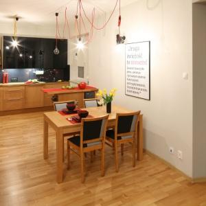 We wnętrzu panuje delikatnie loftowy klimat, który w dużej mierze buduje oświetlenie nad stołem jadalnianym. Są to edisonowskie żarówki, zawieszone na czerwonych oplotach. Projekt: Izabela Szewc. Fot. Bartosz Jarosz.