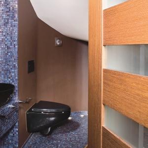 Toaleta pod schodami ma 1,5 m kw. Aby zmieściła się umywalka, przebito ścianę do pomieszczenia obok. Projekt: Joanna Liss. Fot. Tomasz Markowski.