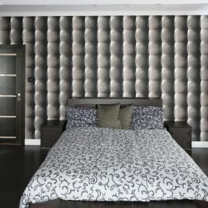 Ściana wykończona oryginalną tapetą sprawia, że wnętrze zyskuje efekt głębi. Spójność do sypialni wnoszą, wyróżniające się tym samym wzorem zasłony oraz narzuta łóżka. Projekt: Karolina Łuczyńska. Fot. Bartosz Jarosz
