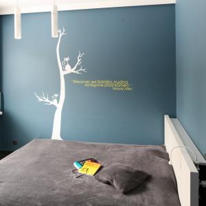 Sypialnia zaaranżowana w minimalistycznym stylu. Meble ograniczono tu do minimum, a jednak aranżacja jest pełna wyrazu. To za sprawą dekoracyjnej ściany z cytatem. Projekt: Katarzyna Karpińska-Piechowicz. Fot. Bartosz Jarosz.