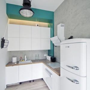 Ściany w kuchni wykończono płytami z betonu dekoracyjnego, który idealnie harmonizuje z technicznym oświetleniem i bielonym drewnem na podłodze.Fot. RED Real Estate Development.